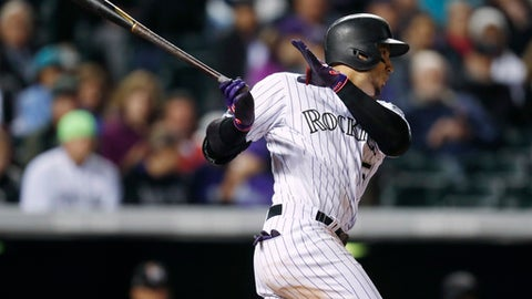 Colorado Rockies' Carlos Gonzalez follows the flight of his double off Miami Marlins starting pitcher Jose Urena to lead off the bottom of the fifth inning of a baseball game Tuesday, Sept. 27, 2017, in Denver. The Rockies won 6-0. (AP Photo/David Zalubowski)
