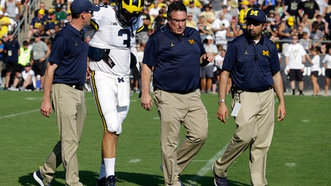 "FILE - In this Saturday, Sept. 23, 2017, file photo, Michigan quarterback Wilton Speight is helped odd the field after being injured during the first half of an NCAA college football game against Purdue in West Lafayette, Ind. He left the stadium for X-rays and coach Jim Harbaugh later referred to it as a ""soft tissue"" injury. Speight did not return to the game and Harbaugh said he wouldn't play this week _ if he Wolverines (4-0, 1-0) had a game. (AP Photo/Michael Conroy, File)"