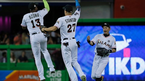 Miami Marlins' Marcell Ozuna (13) Giancarlo Stanton (27) and Ichiro Suzuki, right, of Japan, celebrate after they defeated the Atlanta Braves in a baseball game, Friday, Sept. 29, 2017, in Miami. (AP Photo/Wilfredo Lee)