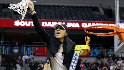 FILE - In this April 2, 2017, file photo, South Carolina coach Dawn Staley holds up the net as she and the team celebrate their win over Mississippi State in the final of NCAA women's Final Four college basketball tournament in Dallas. South Carolina won 67-55. Staley and her champion South Carolina Gamecocks are still waiting for their invite to the White House.  Staley told The Associated Press on Friday night, Sept. 30, that she isn't even sure her team would go now if invited. (AP Photo/LM Otero, File)