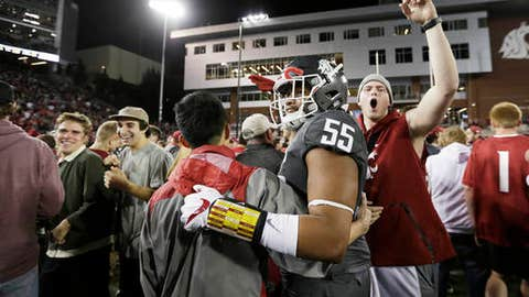 Washington State linebacker Derek Moore (55) celebrates with fans after his team won an NCAA college football game against Southern California in Pullman, Wash., Friday, Sept. 29, 2017. Washington State won 30-27. (AP Photo/Young Kwak)