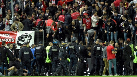 Stadium stewards and police officers gather to help wounded Lille' supporters following the fall of a barrier during a French League One soccer match between Amiens and Lille in Amiens, northern France, Saturday, Sept. 30, 2017. Three Lille supporters have been seriously injured and taken to hospital after a barrier collapsed during the side's football match at Amiens. Lille says 17 other fans were also injured. (AP Photo)