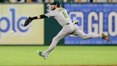 Oakland Athletics second baseman Jed Lowrie (8) can't reach the single hit by Texas Rangers' Jared Hoying during the sixth inning of a baseball game in Arlington, Texas, Saturday, Sept. 30, 2017. (AP Photo/LM Otero)