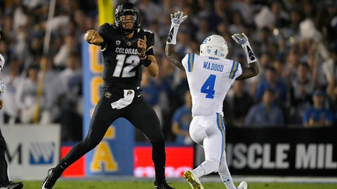 Colorado quarterback Steven Montez, left, passes as UCLA defensive back Jaleel Wadood defends during the first half of an NCAA college football game, Saturday, Sept. 30, 2017, in Pasadena, Calif. (AP Photo/Mark J. Terrill)