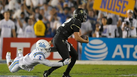 Colorado quarterback Steven Montez, right, escapes a tackle by UCLA linebacker Josh Woods during the second half of an NCAA college football game, Saturday, Sept. 30, 2017, in Pasadena, Calif. UCLA won 27-23. (AP Photo/Mark J. Terrill)