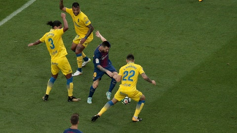 Barcelona's Lionel Messi, center, is challenged by Las Palmas' Ximo Navarro during the Spanish La Liga soccer match between Barcelona and Las Palmas at the Camp Nou stadium in Barcelona, Spain, Sunday, Oct. 1, 2017. Barcelona's Spanish league game against Las Palmas is played without fans amid the controversial referendum on Catalonia's independence. (AP Photo/Manu Fernandez)