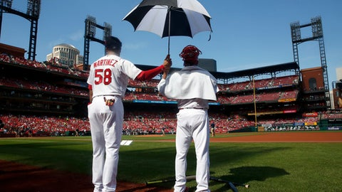St. Louis Cardinals' Jose Martinez, left, holds an umbrella for teammate Carlos Martinez as Carlos Martinez stands on the field following the singing of the national anthem and before the start of a baseball game against the Milwaukee Brewers Sunday, Oct. 1, 2017, in St. Louis. (AP Photo/Jeff Roberson)