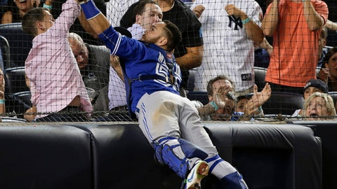 FILE - In this Friday, Aug. 7, 2015 file photo, Toronto Blue Jays catcher Russell Martin (55) catches a pop foul by New York Yankees' Stephen Drew as he leaps against the backstop netting during the seventh inning of a baseball game at Yankee Stadium in New York. The New York Yankees plan to expand protective netting at their home ballpark and spring training complex next year. The team announced the decision during its final regular-season game Sunday, Oct. 1, 2017 against Toronto. (AP Photo/Julie Jacobson)