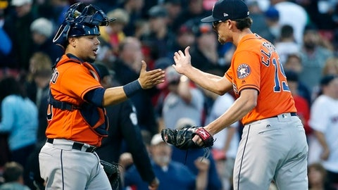 Houston Astros' Tyler Clippard (19) and Juan Centeno celebrate after defeating the Boston Red Sox 4-3 during a baseball game in Boston, Sunday, Oct. 1, 2017. (AP Photo/Michael Dwyer)