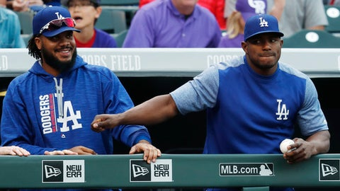 Los Angeles Dodgers relief pitcher Kenley Jansen, left, jokes with right fielder Yasiel Puig as they lean on the dugout rail to look on against the Colorado Rockies in the ninth inning of a baseball game Sunday, Oct. 1, 2017, in Denver. The Dodgers won 6-3. (AP Photo/David Zalubowski)