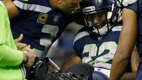 Seattle Seahawks quarterback Russell Wilson, left, comforts running back Chris Carson before Carson is taken away on a cart after suffering an injury in the second half of an NFL football game against the Indianapolis Colts, Sunday, Oct. 1, 2017, in Seattle. (AP Photo/Elaine Thompson)