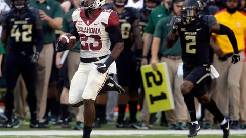 FILE - In this Saturday, Sept. 23, 2017, file photo, Oklahoma running back Abdul Adams (23) breaks away to score a touchdown against Baylor safety Taion Sells (2) during the first half of an NCAA college football game in Waco, Texas. It's not quite the tandem of Samaje Perine and Joe Mixon, but Oklahoma's running back combination of Abdul Adams and Trey Sermon is getting the job done. (AP Photo/LM Otero, File)