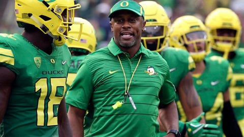 FILE - In this Sept. 2, 2017, file photo, Oregon coach Willie Taggart, center, joins his team as they take the field for an NCAA college football game against Southern Utah in Eugene, Ore.  A number of Pac-12 teams are addressing penalty problems going into the halfway mark of the season. Oregon is among the nation's worst teams when it comes to penalties, with UCLA also seeing lots of yellow flags. (AP Photo/Chris Pietsch, File)