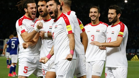 FILE - In this June 7, 2017 file photo, Syria's Mardek Mardkian, second from left, celebrates a goal with teammates during their international friendly soccer match against Japan in Tokyo. Regardless of how Syria does in its World Cup playoff against Australia, the team has helped football knock fighting out the headlines for a while in their war-torn country. The Syrians are still in contention to qualify for the World Cup for the first time, and the journey to their biggest match so far has captured domestic and international attention.(AP Photo/Shuji Kajiyama, File)