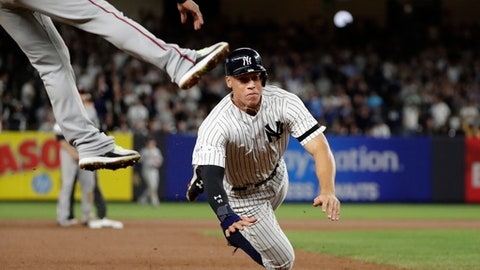 New York Yankees' Aaron Judge slides past Minnesota Twins third baseman Eduardo Escobar on a single by Gary Sanchez during the seventh inning of the American League wild-card baseball game Tuesday, Oct. 3, 2017, in New York. (AP Photo/Frank Franklin II)
