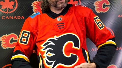Jaromir Jagr puts on a team jersey as he is introduced as the newest Calgary Flames player, at a news conference in Calgary, Alberta, Wednesday, Oct. 4, 2017. The 45-year-old Jagr agreed to a one-year deal Wednesday for his 24th NHL season–and first with a Canadian team. (Larry MacDougal/The Canadian Press via AP)