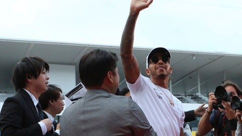 Mercedes driver Lewis Hamilton of Britain greets fans during a fan meeting ahead of the Japanese Formula One Grand Prix at the Suzuka Circuit in Suzuka, central Japan Thursday, Oct. 5, 2017. (AP Photo/Eugene Hoshiko)