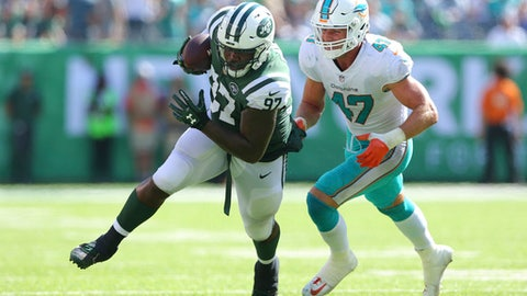 FILE - In this Sept. 24, 2017, file photo, New York Jets defensive end Lawrence Thomas (97) carries the ball against Miami Dolphins linebacker Kiko Alonso (47) during an NFL game at MetLife Stadium in East Rutherford, N.J. Lawrence Thomas is no longer a secret weapon for the Jets. The big defensive lineman has also been used through the first few weeks of the season on offense as a fullback, and even had a 15-yard reception against Miami two weeks ago.  (AP Photo/Brad Penner)