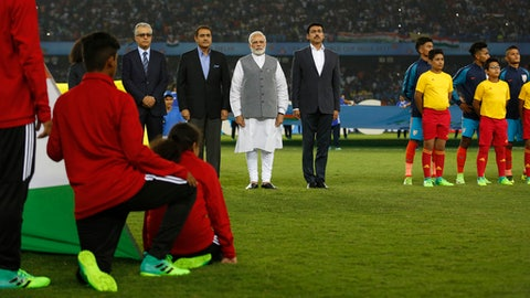 Indian Prime Minister Narendra Modi, in white, stands with other officials for the national anthem before the start of the FIFA U-17 World Cup match between India and the U.S. in New Delhi, India, Friday, Oct. 6, 2017. (AP Photo/Tsering Topgyal)