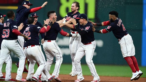 Cleveland Indians' Yan Gomes, center, is mobbed by teammates after the Indians defeated the New York Yankees 9-8 in 13 innings in Game 2 of a baseball American League Division Series, Friday, Oct. 6, 2017, in Cleveland. (AP Photo/David Dermer)