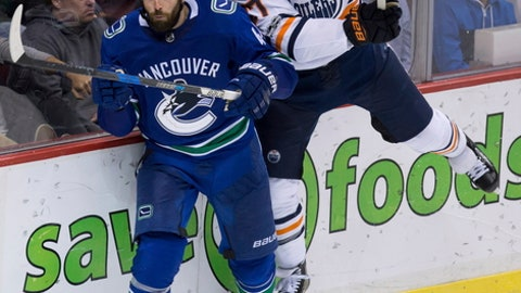 Edmonton Oilers' Milan Lucic, right, checks Vancouver Canucks' Erik Gudbranson during the second period of an NHL hockey game in Vancouver, British Columbia, Saturday, Oct. 7, 2017. (Darryl Dyck/The Canadian Press via AP)