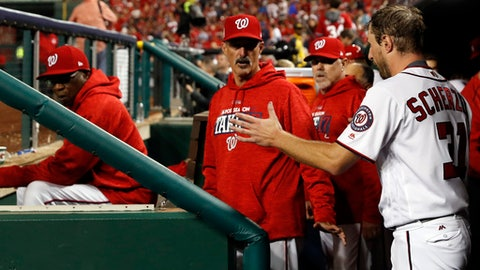 Washington Nationals relief pitcher Max Scherzer talks to pitching coach Mike Maddux, center, as manager Dusty Baker, left, listens, in the dugout in the middle of the fifth inning in Game 5 of baseball's National League Division Series against the Chicago Cubs, at Nationals Park, Thursday, Oct. 12, 2017, in Washington.  (AP Photo/Alex Brandon)