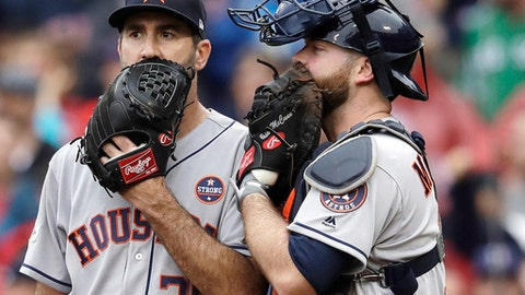 FILE - In this Oct. 9, 2017, file photo, Houston Astros relief pitcher Justin Verlander, left, and catcher Brian McCann talk during the fifth inning of Game 4 of baseball's American League Division Series against the Boston Red Sox in Boston. When a starter is called in to pitch in relief, his routine can be a lot different, and perhaps more importantly, he's often working on short rest. So far in this postseason, the results have been decidedly mixed.(AP Photo/Charles Krupa, File)