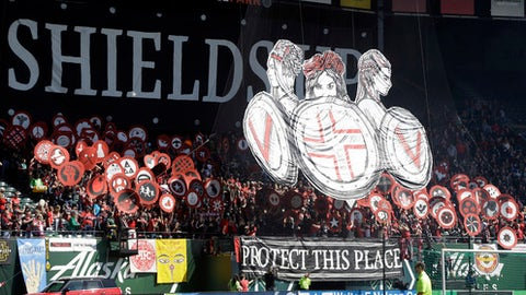 FILE - In this April 15, 2017, file photo, Portland Thorns fans display a large sign and shields before an NWSL soccer match against the Orlando Pride in Portland, Ore. The Portland Thorns will play the North Carolina Courage on Saturday, Oct. 14, 2017 in Orlando, Florida, for the National Women's Soccer League championship. (AP Photo/Don Ryan, File)