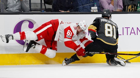 Detroit Red Wings defenseman Xavier Ouellet, left, falls against Vegas Golden Knights center Jonathan Marchessault during the first period of an NHL hockey game Friday, Oct. 13, 2017, in Las Vegas. (AP Photo/John Locher)
