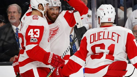 Detroit Red Wings left wing Darren Helm, left, celebrates with center Henrik Zetterberg, center, after Zetterberg scored against the Vegas Golden Knights during the second period of an NHL hockey game Friday, Oct. 13, 2017, in Las Vegas. (AP Photo/John Locher)
