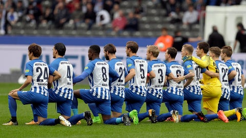Players of Berlin kneel down prior to the German Bundesliga soccer match between Hertha BSC Berlin and FC Schalke 04 in Berlin, Germany, Saturday, Oct. 14, 2017. Hertha Berlin nodded to social struggles in the United States by kneeling before its Bundesliga game at home to Schalke on Saturday. Hertha's starting lineup linked arms and took a knee on the pitch, while coaching staff, officials and substitutes took a knee off it. The action was intended to show solidarity with NFL players who have been demonstrating against discrimination in the US by kneeling, sitting or locking arms through the anthem before games.  (AP Photo/Michael Sohn)