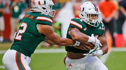 Miami quarterback Malik Rosier (12) hands off to running back Travis Homer (24) during the first half of an NCAA College football game against Georgia Tech, Saturday, Oct. 14, 2017 in Miami Gardens, Fla. (AP Photo/Wilfredo Lee)