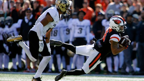 Oregon State wide receiver Trevon Bradford, right, makes a diving catch past Colorado's Jay Irvine, left, during the first half an NCAA college football game, in Corvallis, Ore., Saturday, Oct. 14, 2017. (AP Photo/Timothy J. Gonzalez)