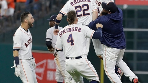 Houston Astros' Carlos Correa celebrates with teammates after hitting a double that scored the game-winning run during the ninth inning of Game 2 of baseball's American League Championship Series against the New York Yankees Saturday, Oct. 14, 2017, in Houston. The Astros won 2-1 to take a 2-0 lead in the series. (AP Photo/David J. Phillip)