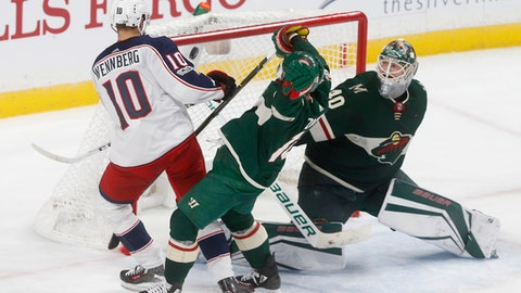 Columbus Blue Jackets' Alexander Wennberg, left, of Sweden, scores the winning goal in overtime against Minnesota Wild goalie Devan Dubnyk, right, during an NHL hockey game Saturday, Oct. 14, 2017, in St. Paul, Minn. The Blue Jackets won 5-4. (AP Photo/Jim Mone)