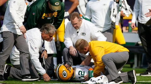 Green Bay Packers quarterback Aaron Rodgers (12) is attended to by medical staff after being hit by Minnesota Vikings outside linebacker Anthony Barr (55) in the first half of an NFL football game in Minneapolis, Sunday, Oct. 15, 2017. (AP Photo/Bruce Kluckhohn)