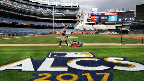 A groundskeeper mows the grass around a recently painted field logo before an American League Championship Series baseball workout day at Yankee Stadium in New York, Sunday, Oct. 15, 2017. (AP Photo/Kathy Willens)