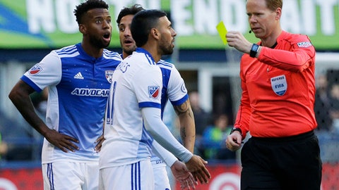 Referee Drew Fisher, right, shows a yellow card to FC Dallas midfielder Javier Morales, center, for a foul on Seattle Sounders midfielder Victor Rodriguez (not shown) in the first half of an MLS soccer match, Sunday, Oct. 15, 2017, in Seattle. (AP Photo/Ted S. Warren)