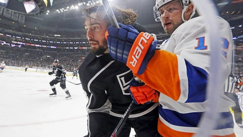 Los Angeles Kings defenseman Drew Doughty (8) loses his helmet but keeps on playing, clearing the puck against New York Islanders right winger Josh Bailey (12) in the third period of an NHL hockey game in Los Angeles, Sunday, Oct. 15, 2017. The Kings won, 3-2. (AP Photo/Reed Saxon)