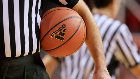 FILE - In this Jan. 24, 2015, file photo, an official holds an Adidas basketball during an NCAA college basketball game between Michigan State and Nebraska in Lincoln, Neb. The spate of arrests, the details of under-the-table bribes to teenagers and the expected downfall of one of the sport's best-known coaches has triggered uncomfortable soul searching among universities that run the nation's most prominent college basketball programs. A top Adidas marketing executive was among the 10 people arrested, after authorities spent two years untangling schemes, often bankrolled with money from apparel companies, to steer future NBA players toward particular sports agents and financial advisers.  (AP Photo/Nati Harnik)