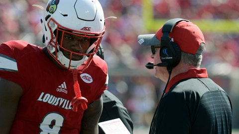 FILE - In this Oct. 14, 2017, file photo, Louisville head coach Bobby Petrino, right, talks with quarterback Lamar Jackson (8) during the second half of an NCAA college football game against Boston College, in Louisville, Ky. Boston College won 45-42. Toss out automatic wins against Kent State and Murray State and Louisville is 2-3 against Power Five competition, after finishing last season with three straight losses. (AP Photo/Timothy D. Easley, File)