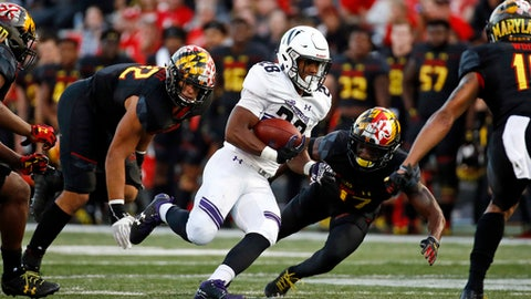 FILE - In this Saturday, Oct. 14, 2017, file photo, Northwestern running back Jeremy Larkin, center, rushes past Maryland defenders in the second half of an NCAA college football game in College Park, Md. After giving up 37 points and 531 yards to Northwestern last week, Maryland needs to improve its defense in a hurry before facing No. 5 Wisconsin on Saturday.  (AP Photo/Patrick Semansky, File)