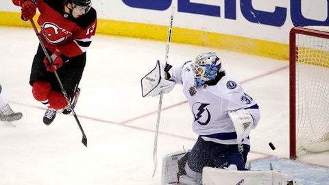 New Jersey Devils center Nico Hischier, left, of Switzerland, jumps out to screen a shot from a teammate as Tampa Bay Lightning goalie Peter Budaj, of Slovakia, (31) deflects the shot during the third period of an NHL hockey game, Tuesday, Oct. 17, 2017, in Newark, N.J. The Devils won 5-4 in a shootout. (AP Photo/Julio Cortez)