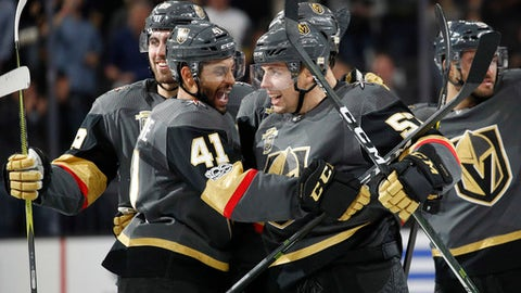 Vegas Golden Knights' Pierre-Edouard Bellemare, left, celebrates with David Perron after Perron made the game-winning goal during overtime of an NHL hockey game against the Buffalo Sabres, Tuesday, Oct. 17, 2017, in Las Vegas. (AP Photo/John Locher)