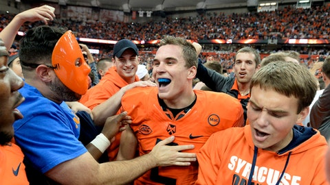 FILE - In this Friday, Oct. 13, 2017, file photo, Syracuse quarterback Eric Dungey center, celebrates with fans after Syracuse's 27-24 win over Clemson in an NCAA college football game in Syracuse, N.Y. Clemson has fallen, Miami is on the rise. Upsets, last-minute victories have made it a free-for-all race for the Atlantic Coast Conference crown, and there some unexpected contenders in the mix. (AP Photo/Adrian Kraus, File)