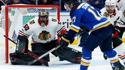 St. Louis Blues' Jaden Schwartz tries to get off a shot as Chicago Blackhawks goalie Corey Crawford, left, and Brent Seabrook (7) defend during the second period of an NHL hockey game Wednesday, Oct. 18, 2017, in St. Louis. (AP Photo/Jeff Roberson)