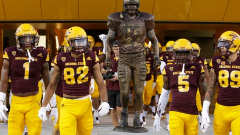 FILE - In this Aug. 31, 2017, file photo, players file past the Pat Tillman statue, with one reaching to touch it, at an NCAA college football game between Arizona State and New Mexico State in Tempe, Ariz. Ever since Arizona State unveiled a statute of former defensive back Pat Tillman outside the school's student-athlete facility just before the season, the Sun Devils have made a point of touching the statue as they head to the field before every home game. (AP Photo/Rick Scuteri, File)