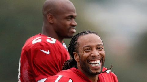 Wide receiver Larry Fitzgerald, right, and running back Adrian Peterson of the Arizona Cardinals laugh during an NFL training session at the London Irish rugby team training ground in the Sunbury-on-Thames suburb of south west London, Thursday, Oct. 19, 2017. The Arizona Cardinals are preparing for an NFL regular season game against the Los Angeles Rams in London on Sunday. (AP Photo/Kirsty Wigglesworth)