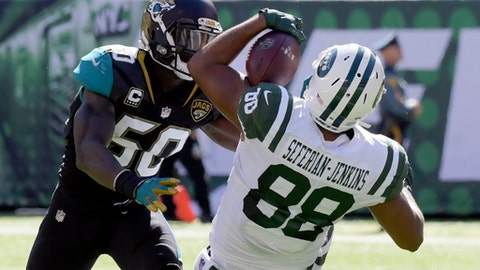 FILE - In this Oct. 1, 2017, file photo, New York Jets' Austin Seferian-Jenkins, right, makes a catch in front Jacksonville Jaguars' Telvin Smith during the first half of an NFL football game in East Rutherford, N.J. Seferian-Jenkins 23 catches over the last four games lead NFL tight ends, not bad for a guy who wondered a year ago if he'd ever play football again.  (AP Photo/Bill Kostroun, File)