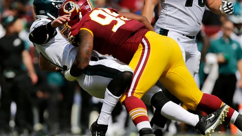 FILE - In this Sept. 10, 2017, file photo, Washington Redskins defensive end Jonathan Allen, right, knocks down Philadelphia Eagles quarterback Carson Wentz as Wentz throws a pass in the first half of an NFL football game in Landover, Md.  A foot injury likely ends the promising rookie season of the Redskins first-round pick Jonathan Allen and puts more onus on the rest of the young players on the defensive line to compensate for the loss of his production. (AP Photo/Mark Tenally, File)